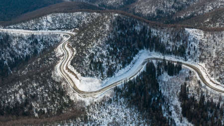 Aerial view of the river and taiga forests and road in the winter - springtime . Abstract landscape of northern nature with drone. Stockfoto
