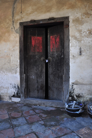 Open old door leading into a dark entrance photo