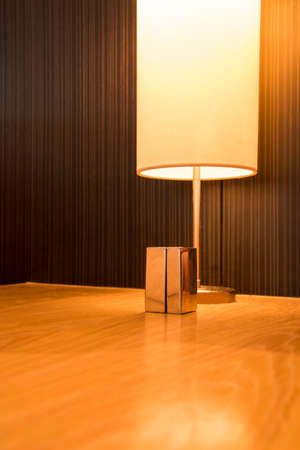 Metal bottel and warm lamp on table.
