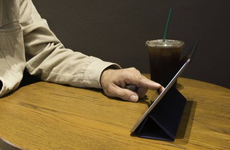 Man play tablet in coffee shop.