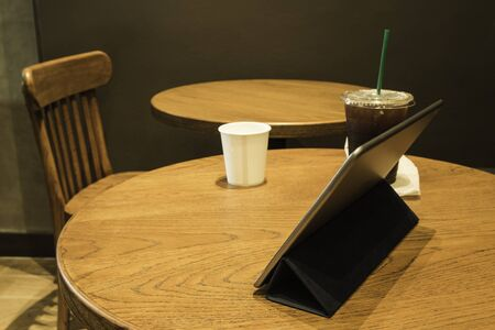 Tablet and coffee on table.