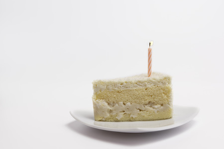 Piece of dessert coconut cake and candel for birthday on white plate and isolated white backgroud. Фото со стока