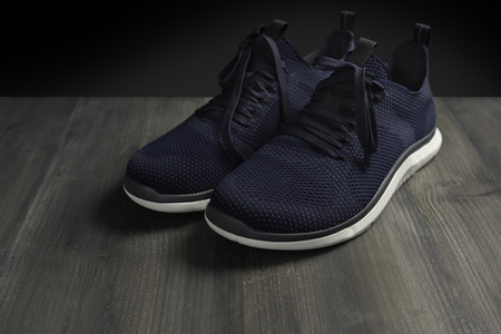 Footwear modern running sport shoes pair on dark wooden and isolated black background. Фото со стока