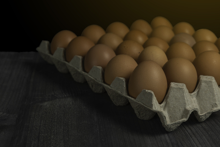 Raw chicken eggs in paper container on dark wood table background. Фото со стока