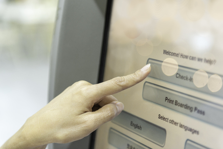 Check-in by self on kiosk machine. Close-up of female finger to touch the screen of kiosk machine for self-service check-in at airport building. Stock Photo