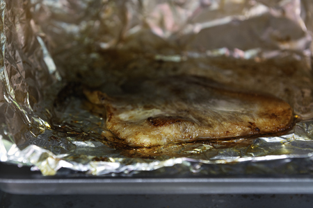 Grilled Pork in Electric Oven On a tray with aluminum foil.