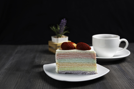 Rainbow crape cake on white plate with a cup of hot tea on dark wooden table, isolated black background. Фото со стока