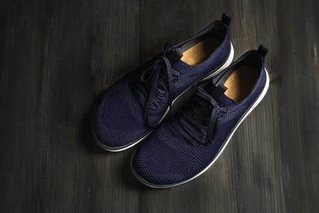 Footwear modern running sport shoes pair on dark wooden.