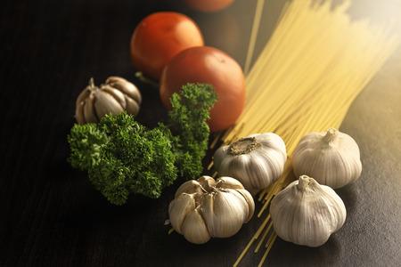 Garlic, Parsley, Tomato and Pasta on dark table.