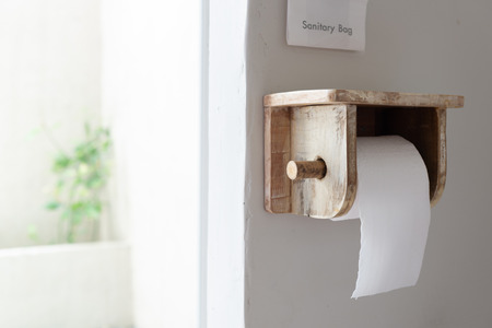 White roll of soft toilet paper hanging made of wood holder on white restroom  wall.
