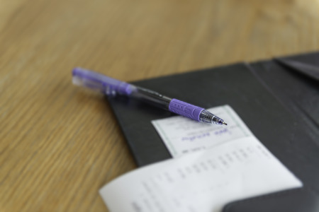 Open leather bill holder, blue pen and paper slips on table in restaruant. Payment expense by credit card.