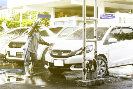 Worker cleaning white car using high pressure water and foam. Фото со стока
