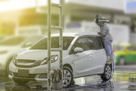 Worker cleaning white car using high pressure water and foam. Banco de Imagens