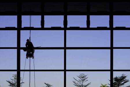 Silhouette of Glass cleaner worker on the ropes washing glass.