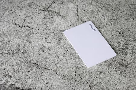 Proximity or RFID card white type thin, flexible, on cement background. Stock fotó