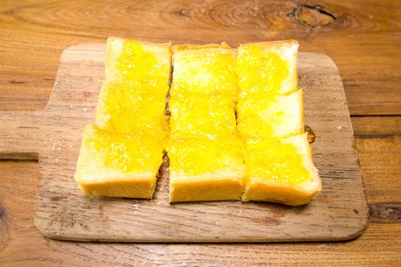 multi grain sandwich: orange jam and white bread on wood plate
