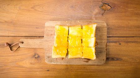 multi grain sandwich: Overhead view of orange jam and white bread on wood plate