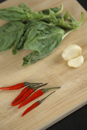 red pepper, garlic, and basil on chopping block