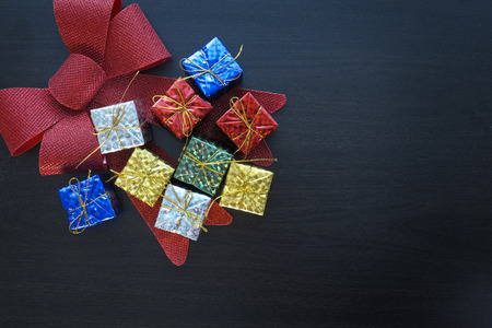 colorful gift box and bow on black wood table