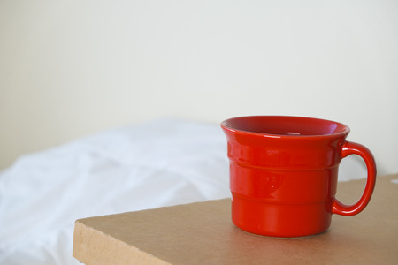 a red cup on brown table with over light on curtain background