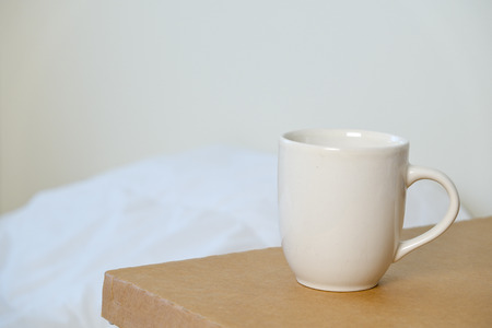 a cup on brown table with white bed background