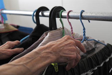 clothing store: woman hand picking colourful of clothes hanging on a rack