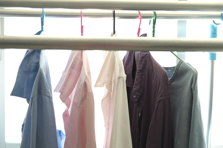 colourful of clothes hanging on a rack with white background