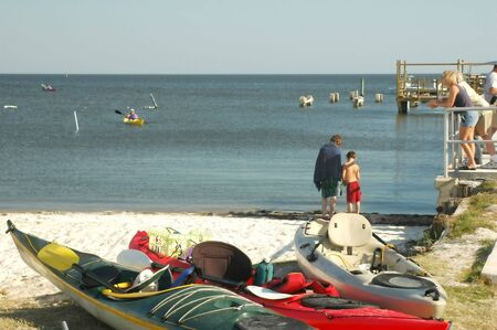 paddler: Kayaks await paddlers on the beach at Cedar Key, Florida on the Gulf of Mexico.