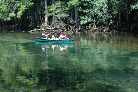 run down: Canoeists paddle down the spring run. Stock Photo