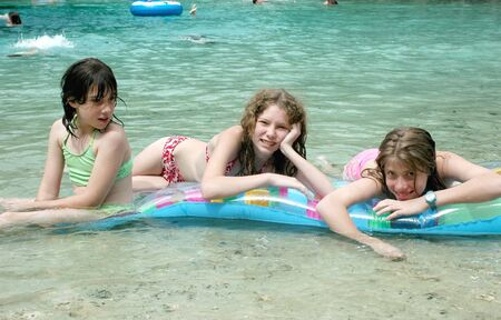Three girls enjoy a day at the spring on their float. Stock fotó