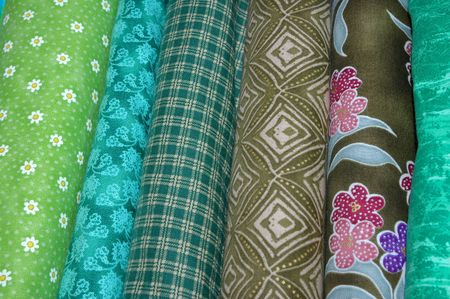 Bolts of quilting fabric in the green range. Foto de archivo