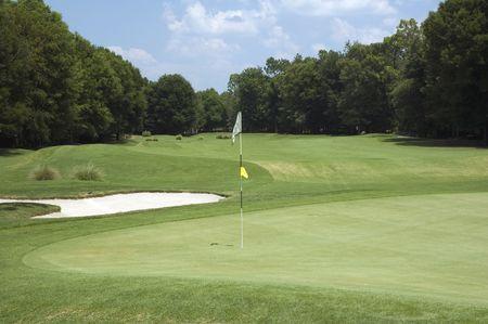A flag marks the hole on the golf course. Фото со стока