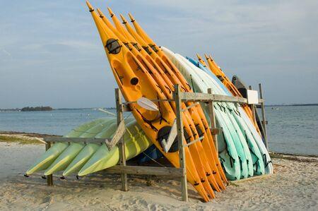Kayaks stacked at a rental facility. Фото со стока