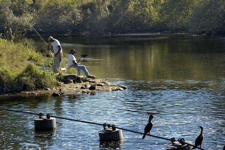 Two black men fish on the river with birds watching.