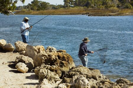Two men catch fish with poles and nets on the riverbank.
