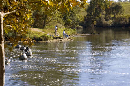 Two black men enjoy fishing the riverbank for freshwater fish. Stock Photo - 687740