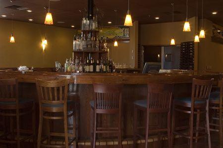 豊富な木製のスツール、ヴィンテージの吊り下げ式の照明および酒の表示バーでチーク材丸棒。