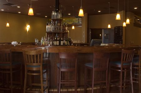 A round teak bar with rich wooden bar stools, vintage pendant lighting and a liquor display.