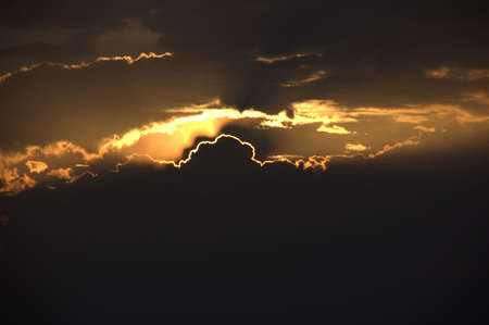 Brilliant rays peek through the clouds at sunset. Banco de Imagens