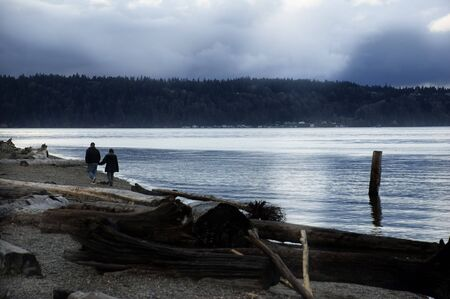 A couple in silhouette walks along a driftwood-covered beach at Point Defiance, Tacoma, Washington in springtime.
