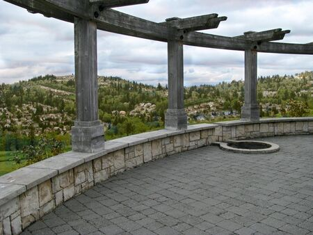 A courtyard with columns with a residentially settled hillside in the distance.