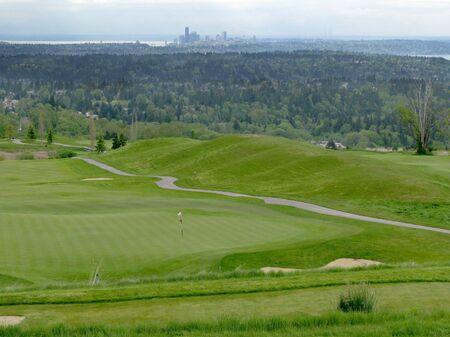 バック グラウンドで、ワシントン州シアトルのスカイラインとフラグと緑のゴルフコース。 写真素材