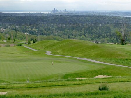 A golf course green with flags with the Seattle, Washington skyline in the background.