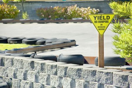 A Yield Sign warns drivers against bumping or reckless driving on a go cart track.