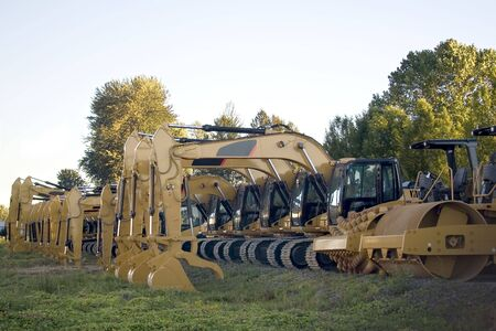 frontend: New steamrollers, bulldozers and front-end loaders in a row on the sales lot.