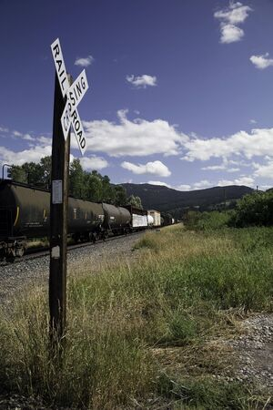 xing: A train pulls tankers and cargo cars across a railroad crossing in Montana. Stock Photo