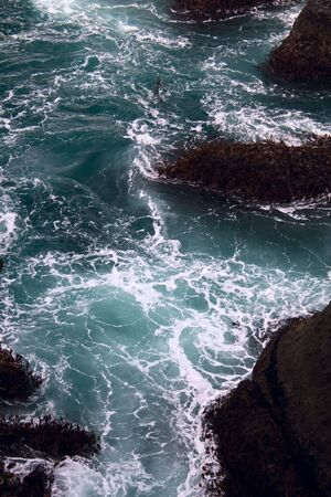 churning: The churning blue Pacific Ocean and rocks on the coast. Stock Photo