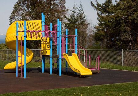 A colorful play set sits empty on a beautiful spring day.