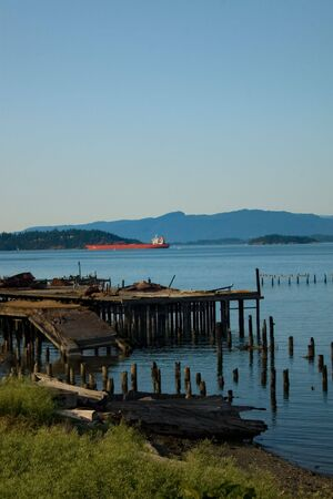puget: A broken dock and an oil tanker in the Puget Sound at Anacortes Island, Washington. Stock Photo
