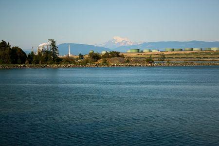 puget sound: Una raffineria di petrolio e le cisterne sul Puget Sound a Isola Anacortes, Washington, con il Monte Baker in lontananza. Archivio Fotografico